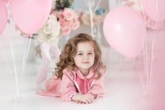 Härlig förskole- flicka i en vit studio med rosa hjärta-formade ballonger arkivfoton