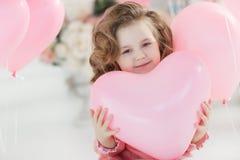 Härlig förskole- flicka i en vit studio med rosa hjärta-formade ballonger arkivbilder