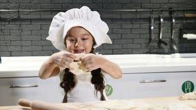 Härlig förtjusande flicka i kockhattlek med deg och mjöl i huskök Barnkockbegrepp Ungar spelar vuxna människor arkivfilmer