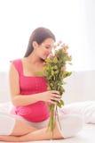 Härlig förväntansfull moder med gulliga rosa blommor Arkivbilder