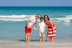 Härlig familj på stranden som gör en självstående fotografering för bildbyråer