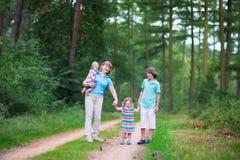 Härlig familj som fotvandrar i ett sörjaträ Fotografering för Bildbyråer