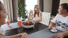 Härlig familj som har frukosten tillsammans i köket hemma Den tonåriga flickan som dricker fruktsaft och hennes fader, är drinkar stock video