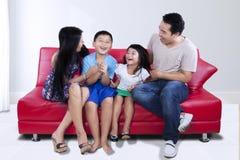 Härlig familj som har gyckel på soffan arkivfoto