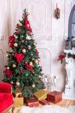 Härlig ferie dekorerade rum med julgranen, spis och med gåvor Hemtrevlig vinterplats inre white Jul Nu royaltyfria foton
