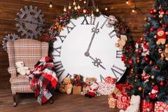 Härlig ferie dekorerade vardagsrum med julgranen och gåvor Stor magisk klocka på träväggen Design för vinterferier royaltyfri fotografi