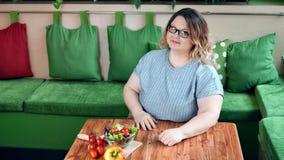 Härlig fet kvinna som tycker om sund grönsaksallad för ny mat på den höga vinkeln för kökhem stock video