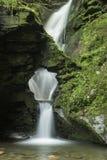 Härlig flödande vattenfall med magisk sagakänsel i frodigt royaltyfri bild