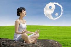 Härlig flickaövningsyoga med ying av det yang molnet arkivbild
