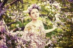 Härlig flicka bland en fjädrablomning Royaltyfri Bild