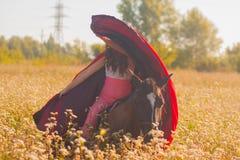 härlig flicka, brunett i en röd regnrock arkivfoton
