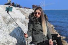 härlig flicka Den moderiktiga flickan gör en selfie på stranden med havet i bakgrunden arkivfoto