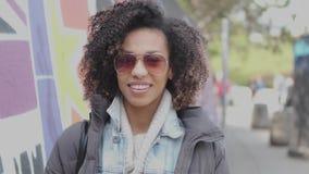 Härlig flicka för blandat lopp med lockigt hår som poserar i stads- stadslandskap arkivfilmer