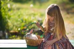 Härlig flicka för gullig bonde i jeans som tycker om sommardag i byliv med blommor som ler happyly med kaninkaninen i korg Royaltyfri Foto