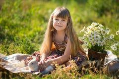 Härlig flicka för gullig bonde i jeans som tycker om sommardag i byliv med blommor som ler happyly med kaninkaninen i korg Royaltyfri Bild