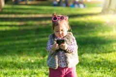 Härlig flicka för liten unge som utomhus använder mobiltelefonen fotografering för bildbyråer