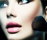 Härlig flicka för modemodell som applicerar makeup Arkivfoto