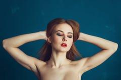 Härlig flicka för närbildstående på en blå bakgrund arkivbild