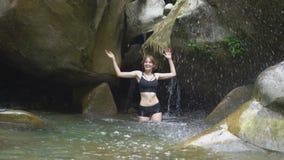 Härlig flicka för ultrarapid som plaskar på vatten vid händer i bergsjön i grön tropisk skog med den lilla vattenfallet arkivfilmer