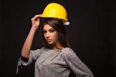 Härlig flicka för ung arbetare som sätter på hjälmskönhet royaltyfri foto