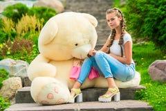 Härlig flicka 20 gamla år med en stor nallebjörn i parkera Arkivfoton