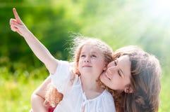 härlig flicka henne liten moder som visar till Fotografering för Bildbyråer