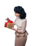 Härlig flicka i aftonklänningen som rymmer en gåva Royaltyfri Bild