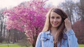 Härlig flicka, i att blomstra träd i vårträdgård stock video