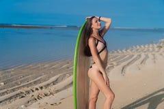 Härlig flicka i baddräkten som poserar på den öde stranden med surfingbrädan på varm sommardag arkivbild