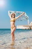 Härlig flicka i bikini, exponeringsglas och hatt i klart havsvatten Arkivbilder