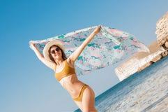 Härlig flicka i bikini, exponeringsglas och hatt i klart havsvatten Arkivbild