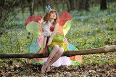 Härlig flicka i bilden av en fjäril royaltyfria foton