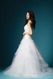 Härlig flicka i bröllopsklänning på blå bakgrund royaltyfri foto
