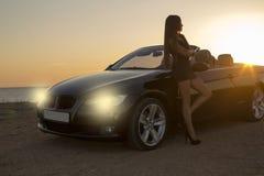 Härlig flicka i den eleganta klänningen som poserar bredvid en cabriolet på solnedgång arkivfoton