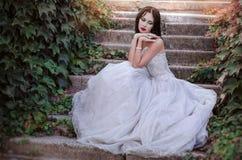 Härlig flicka i den frodiga klänningen i trädgården Attraktiv brunettkvinna i en lång vit klänning som sitter i blommande rosor f Arkivbild