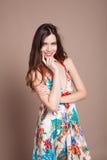 Härlig flicka i den kulöra klänningen som poserar leende arkivbild