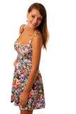 Härlig flicka i den patern korta sommarklänningen för blomma som poserar mot vit Arkivbild
