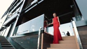 Härlig flicka i den röda formella klänningen som poserar på gatan på Sunny Day stock video