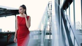 Härlig flicka i den röda formella klänningen som poserar på gatan på Sunny Day arkivfilmer
