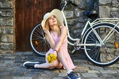 Härlig flicka i den rosa klänningen, sugrörhatt som poserar ståenden som sitter på stenvägen i gammal stad på väggbakgrund bredvi royaltyfria bilder