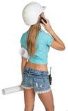 Härlig flicka i den vita hjälmen, kortslutningar med skjortan Arkivfoto