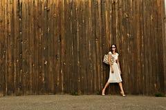 Härlig flicka i den vita klänningen mot väggen Royaltyfria Foton