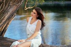 Härlig flicka i elegant klänning och charmiga leendet som poserar för fotografen i parkera av Yekaterinburg Arkivbild