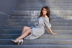 Härlig flicka i elegant klänning och charmiga leendet som poserar för fotografen i staden av Yekaterinburg Arkivfoton
