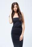 Härlig flicka i en åtsittande svart klänning som isoleras på den vita backgroen Arkivfoto