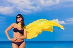 Härlig flicka i en bikiniflicka med en gul torkduk som framkallar Arkivfoto