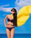 Härlig flicka i en bikiniflicka med en gul torkduk som framkallar Arkivbilder