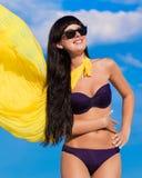 Härlig flicka i en bikiniflicka med en gul torkduk som framkallar Fotografering för Bildbyråer