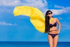 Härlig flicka i en bikiniflicka med en gul torkduk som framkallar Royaltyfri Fotografi