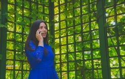 Härlig flicka i en blå klänning under bågen som talar på telefonen Arkivfoto